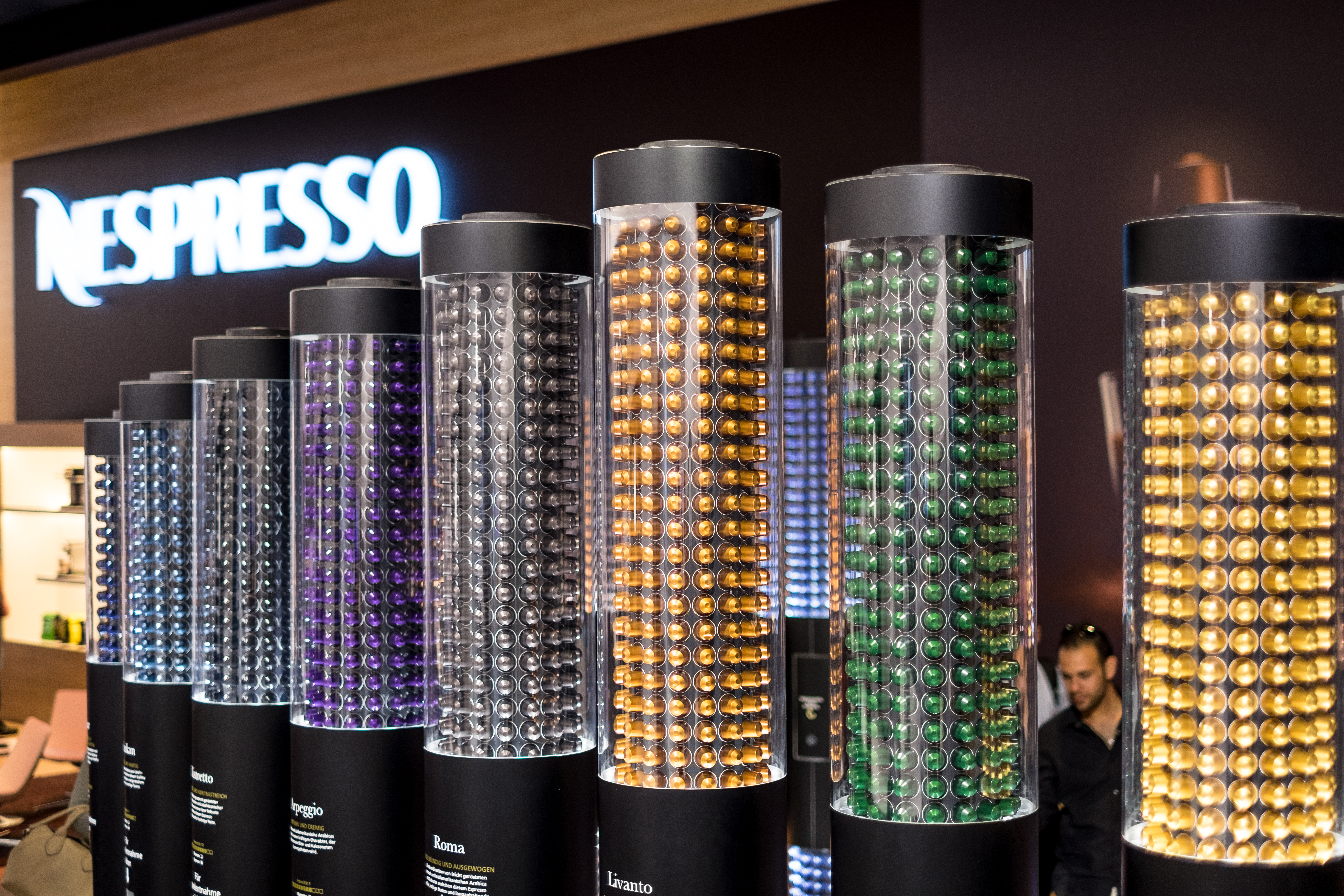A photograph shows a display of all the small, plastic coffee pods made by Nespresso.